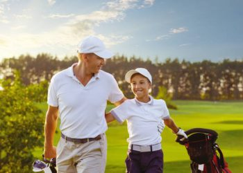 Happy man with his son golfers walking on perfect golf course at summer evening