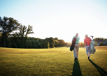 Shot of a retired couple walking across a golf green
