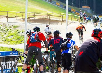 Winterberg, Germany - August 22, 2015: Bikers with montain bikes in cycling and bike park in winter sport area of Winterberg in summertime. Group of men is entering bicycle park. In background some bikers are cycling into forest and to ski lift.