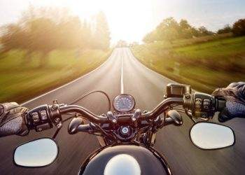 POV shot of young man riding on a motorcycle. Hands of motorcyclist on a street