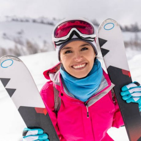 "Portrait of a happy Latin American woman skiing in the Alps and looking at the camera smiling -"" winter sports concepts"