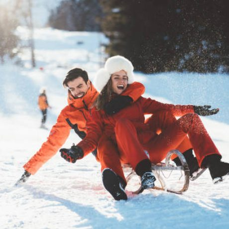 Young couple sledding on sunny day in the mountain