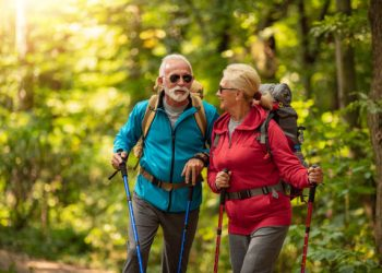 Happy senior couple is hiking in forest.Adventure, travel,hike and people concept.