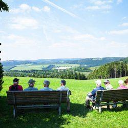 Langewiese, Germany - August 22, 2015: Summershot of seniors having a break on benches at trekking pathway Rothaarsteig in Sauerland. Scene is in Langewiese, small village near to Neuastenberg and Winterberg. Between seniors is an adult woman. Gorup is watching to north.